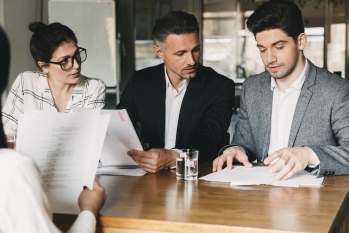trabajar-marca-empleadora-personas-revisando-papeles-mesa-oficina