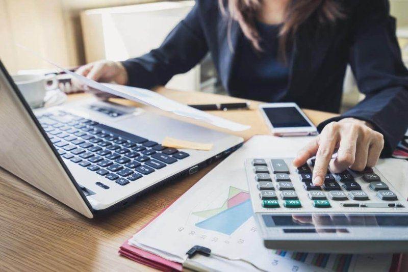 ejecutiva-calculando-documentos-laptop-mesa-transformacion-digital-contabilidad