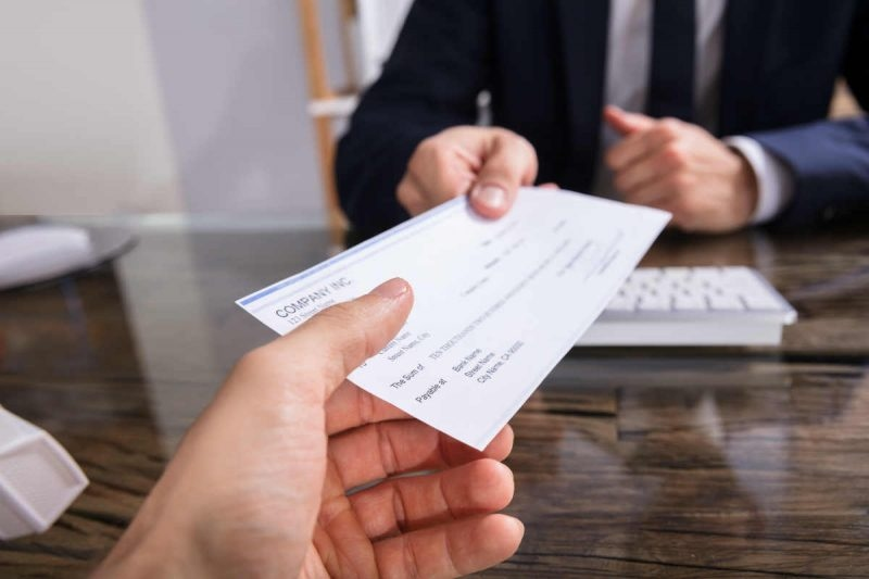 outsourcing-de-remuneraciones-ventajas-empleado-recibiendo-cheque-oficina