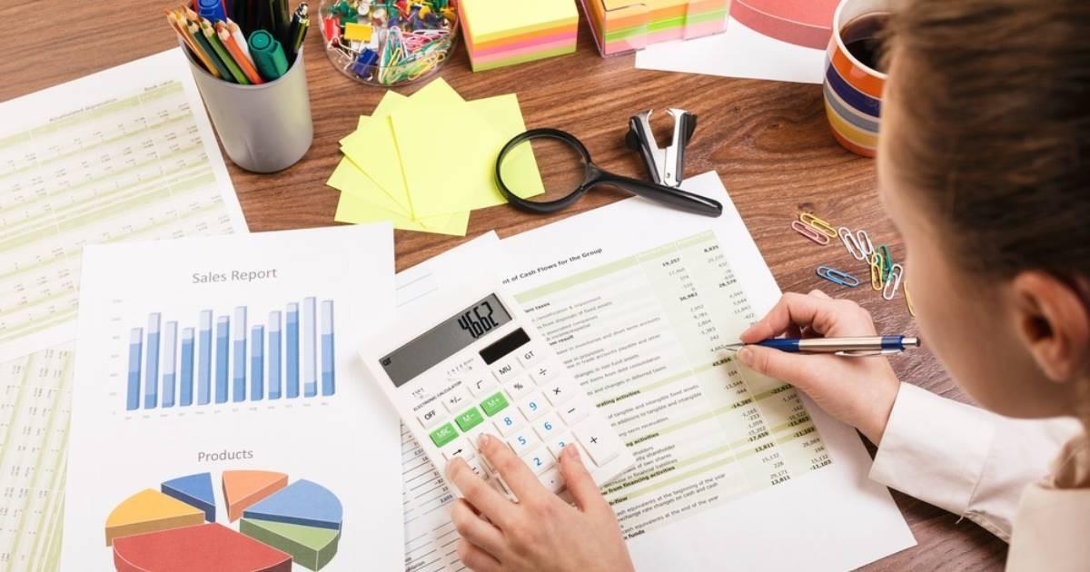 consejos-outsourcing-de-remuneraciones-ejecutiva-calculando-salarios-escritorio-hojas-graficos-calculadora