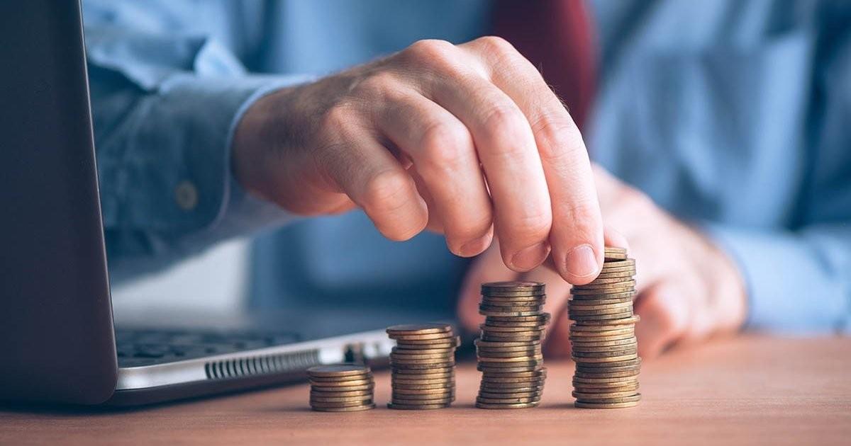 consejos-outsourcing-de-remuneraciones-ejecutivo-apilando-monedas-escritorio-laptop